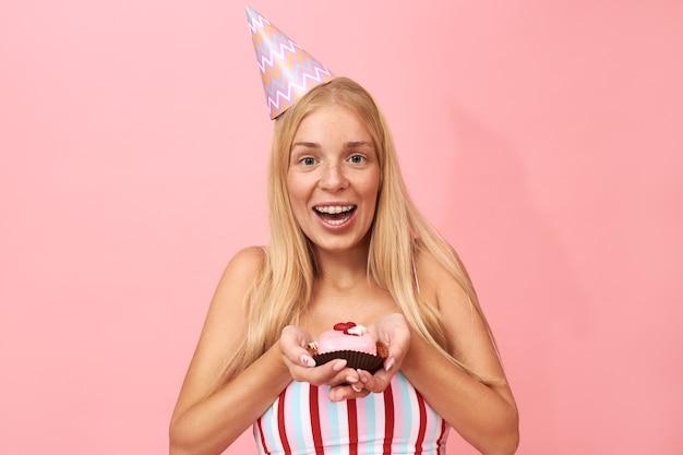 Ritratto di carino affascinante giovane donna con lentiggini, lunghi capelli lisci e bretelle congratulandosi con te per il compleanno