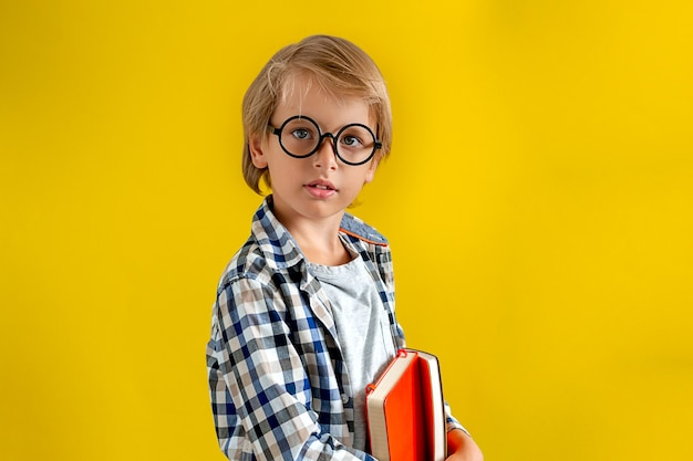 Portrait of cute and clever blonde caucasian boy in a checked shirt on yellow background.