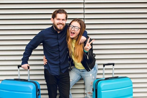 Ritratto di coppia carina in piedi su sfondo grigio a strisce. ha capelli lunghi, occhiali, maglione giallo, giacca. indossa camicia nera, barba. stanno abbracciando e ridendo alla telecamera.