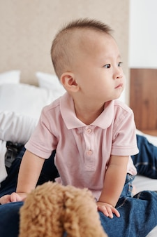 Portrait of cute curious asian baby boy crawling on bed and looking around