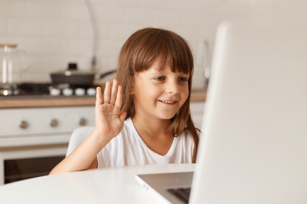 Portrait of cute dark haired female child sitting at table having video call, looking at laptop display and waving hand to notebook webcamera, has positive expression.
