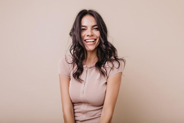 Ritratto di ragazza carina dai capelli scuri con un sorriso bianco come la neve. signora dagli occhi marroni in top beige