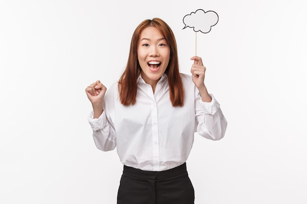 Portrait of cute and excited asian woman have great idea, being inspired, holding comment cloud on stick with beaming smile, sharing her thought, white wall