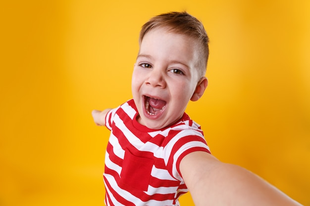 Portrait of a cute excited little boy taking selfie on mobile phone