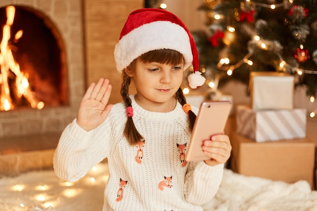 Portrait of cute female child wearing white sweater and santa claus hat, having video call, waving hand to cellphone camera, posing in festive room with fireplace and xmas tree.