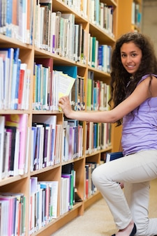 Portrait of a cute female student choosing a book