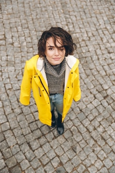 Portrait of cute female in yellow stylish coat looking up on camera while standing on paving stones during her walk