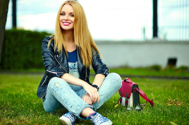 Portrait of cute funny blond modern sexy urban young stylish smiling woman girl model in bright modern cloth outdoors sitting in the park on the green grass in jeans with pink bag