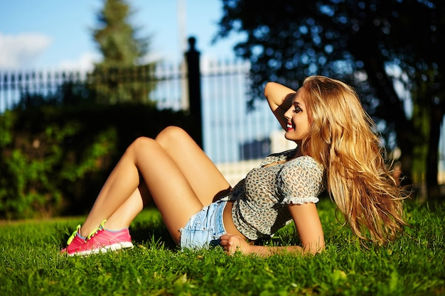 Portrait of cute funny sexy young stylish smiling woman girl model in bright modern cloth with perfect sunbathed body outdoors lying in the park in jeans shorts holding healthy strong hair in hand