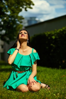 Portrait of cute funny sexy young stylish smiling woman girl model in bright modern green dress with perfect sunbathed body outdoors in the park