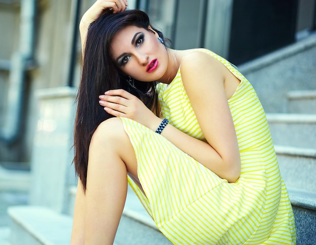 Portrait of cute funny sexy young stylish smiling woman girl model in bright modern yellow dress with perfect sunbathed body outdoors in the park