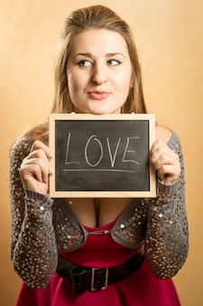 Portrait of cute funny woman holding blackboard with word love