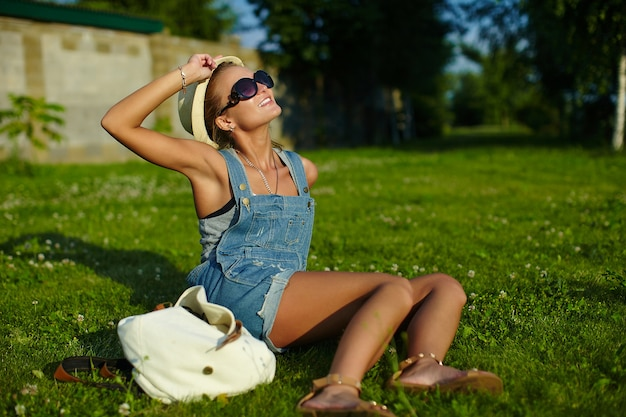 Portrait of cute funny young stylish smiling woman woman model in casual modern cloth with perfect sunbathed body outdoors in the park in hat in glasses sitting on the grass
