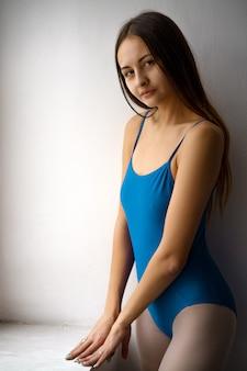 Portrait of a cute girl in a blue bodysuit smiling