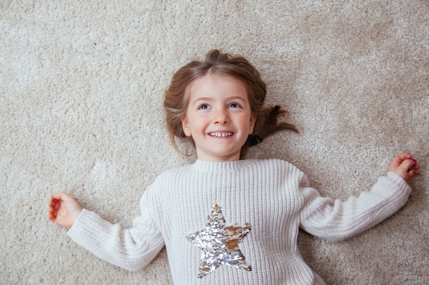 Portrait of a cute girl on the carpet