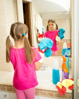 Portrait of cute girl cleaning and polishing mirror at bathroom