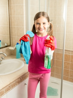Portrait of cute girl doing cleaning at bathroom holding rag and spray