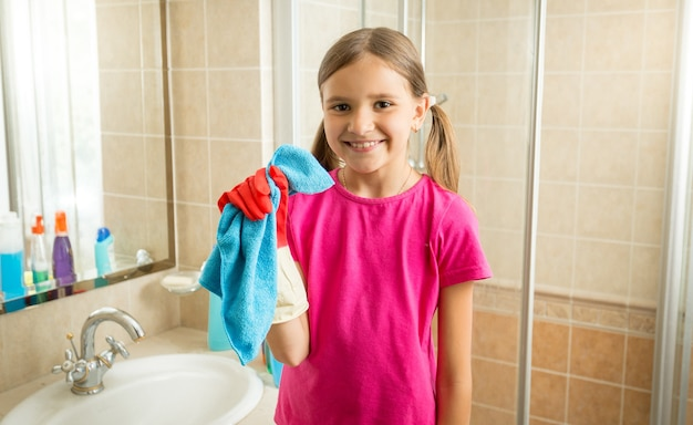 Portrait of cute girl doing cleaning posing with blue rag