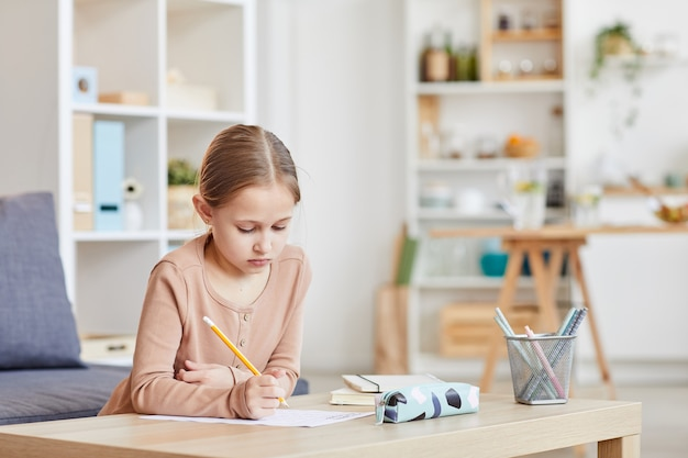 Portrait of cute girl doing homework for elementary school while studying at home in cozy interior, copy space
