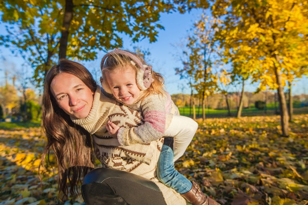 Portrait of cute girl and happy mother have fun in yellow autumn forest on a warm sunny day