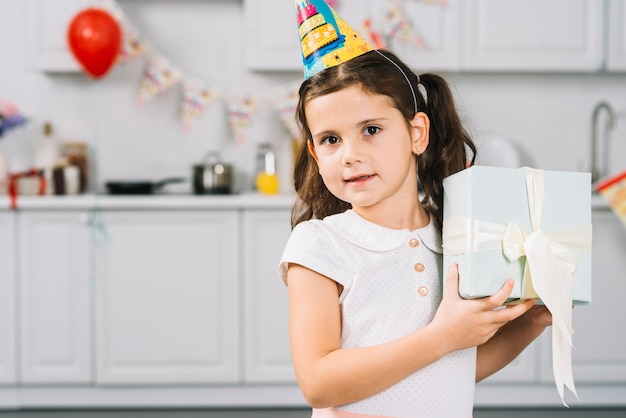 Portrait of a cute girl holding birthday gift in kitchen
