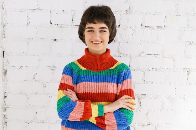 白いレンガの壁の背景の若い白人女性が見える虹のセーターの肖像画かわいい女の子...