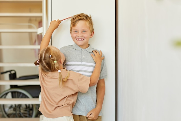 Portrait of cute girl measuring height of happy older brother standing against white wall at home, copy space