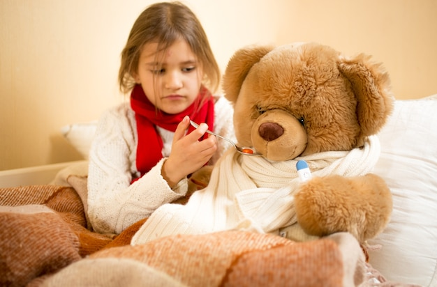 Portrait of cute girl playing and measuring teddy's bear temperature with thermometer