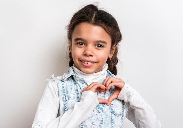 Portrait cute girl showing heart shape