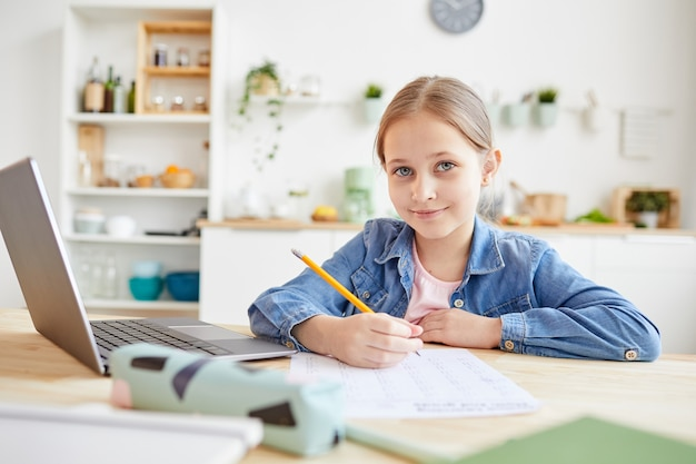Portrait of cute girl smiling at camera while doing homework or tests sitting at wooden desk in cozy home interior, copy space