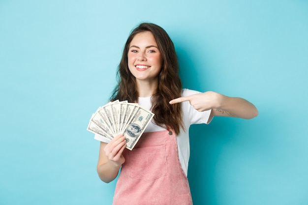 Portrait of cute girl smiling proud and satisfied, pointing finger at money dollar, showing dollar bills, standing over blue background.