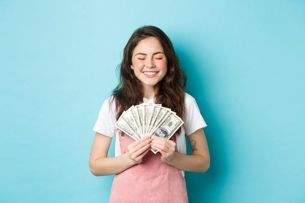 Ritratto di una ragazza carina che sorride con soddisfazione, tiene in mano soldi e sembra soddisfatta, vincendo un premio in banconote da un dollaro, in piedi su sfondo blu.