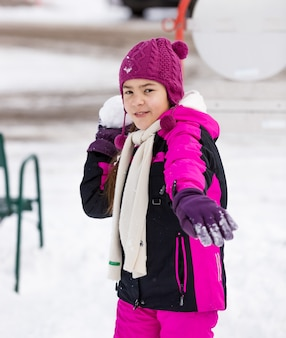 Portrait of cute girl throwing snowball