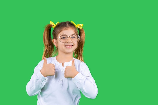 Portrait of a cute girl who shows class smiles and looks at the camera green isolated background and side