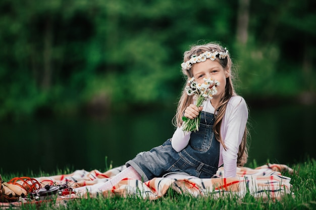 Portrait of a cute girl with a bouquet of daisies