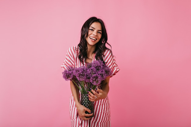 Portrait of cute girl with charming smile. lady in striped top enjoying flowers.