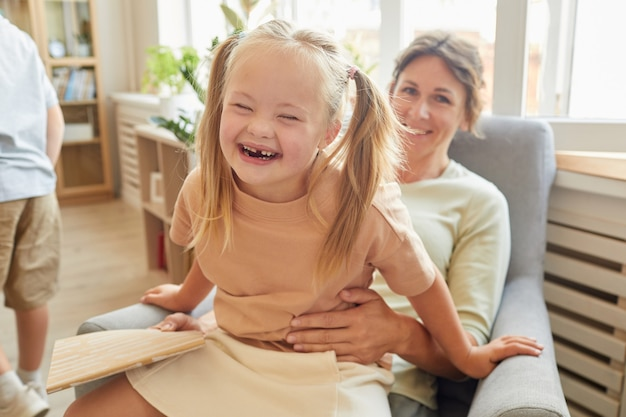 Portrait of cute girl with down syndrome laughing happily while playing with mother at home