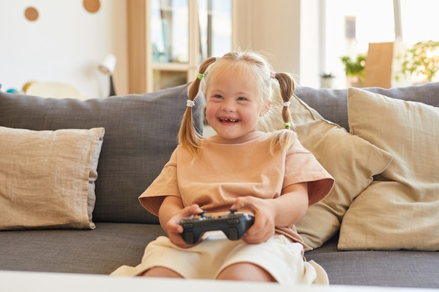 Portrait of cute girl with down syndrome playing video games and laughing happily while sitting on couch in living room, copy space