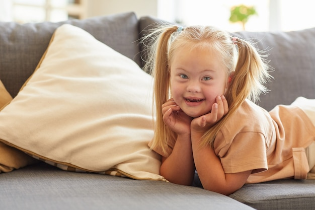 Portrait of cute girl with down syndrome smiling happily at camera while lying on sofa at home, copy space
