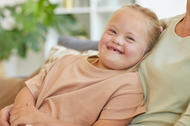 Portrait of cute girl with down syndrome smiling happily at camera with unrecognizable mother embracing her, copy space