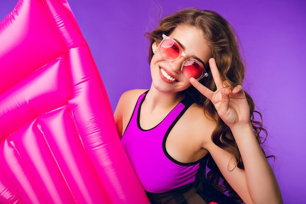 Portrait of cute girl with long curly hair in pink sunglasses smiling to camera on purple background in studio. she wears swimsuit, holds pink air mattress and shows a cool sign.