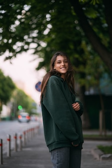Portrait of cute girl with long hair looks at the camera in city on street background.