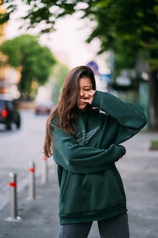 Il ritratto della ragazza sveglia con capelli lunghi esamina la macchina fotografica in città sul fondo della via.