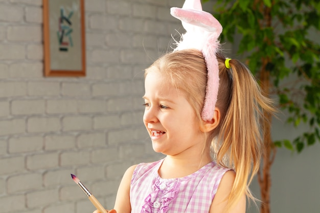 Portrait of a cute girl with paintbrush  ready to paint eggs