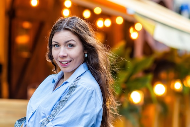 Portrait of a cute and gorgeous women posing on blurred strret surface with bokeh light