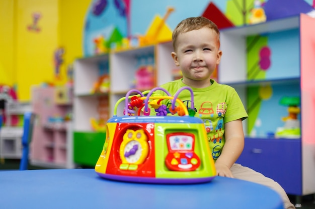 Portrait a cute happy boy is playing with a  bright colorful toy in a children room