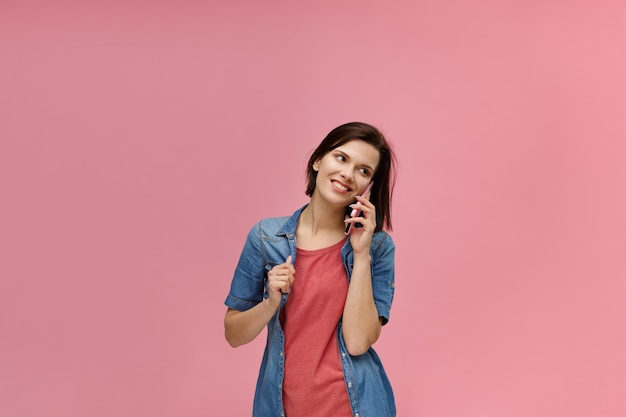 Portrait of cute happy brunette woman wearing t-shirt and jeans shirt talking on mobile phone and smiling isolated over pink background.