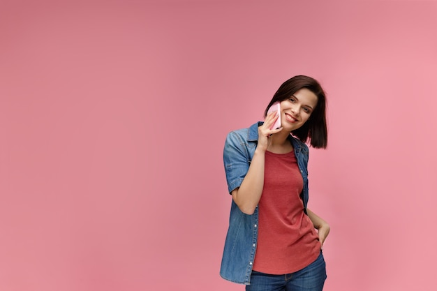 Portrait of cute happy brunette woman wearing t-shirt and jeans shirt talking on mobile phone and smiling isolated over pink background