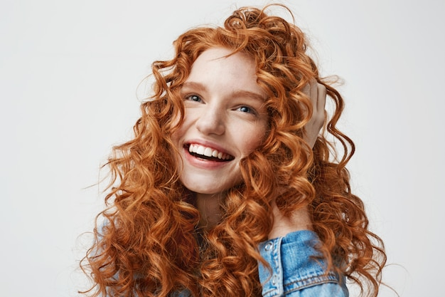 Portrait of cute happy girl smiling touching her curly red hair .