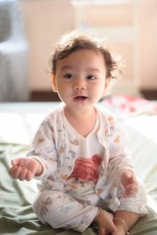 Portrait of a cute happy little asian baby girl she sit on bed and look at camera, baby expression concept